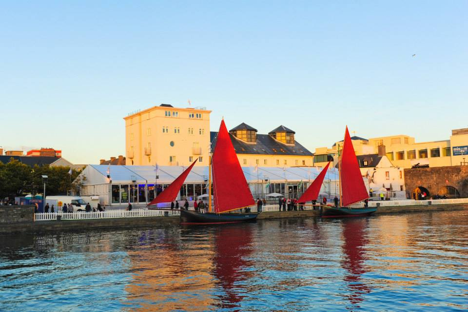 Traditional 'Galway Hooker' sailboats parade past the venue